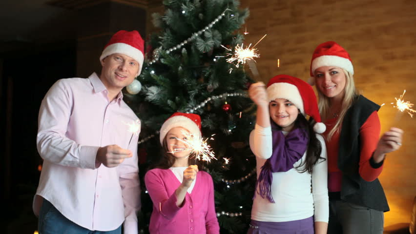 Cheerful family with sparklers celebrating Christmas and New Year