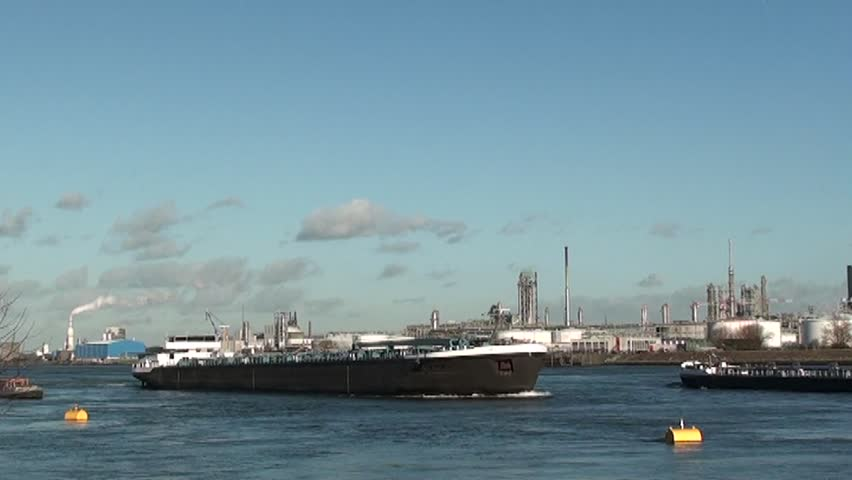 oil tanker in harbor of Rotterdam Netherlands passing by big petrochemical refinery