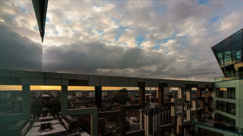 Birmingham sunset to sunrise timelapse. Filmed from within The Cube building in Birmingham, England, the exoskeleton of the construction frames the spectacular sunset through to dawn. 4K original.