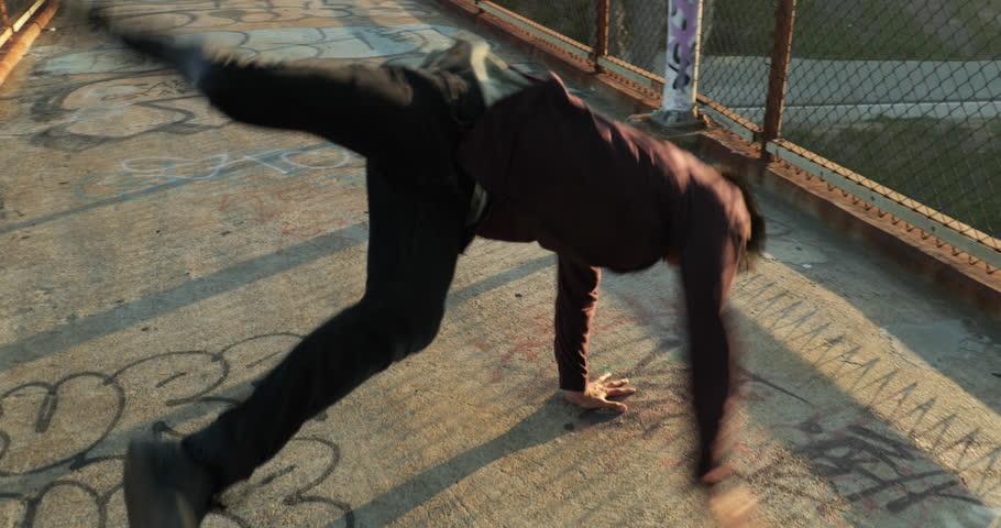Young Happy Asian Man Dancing On Bridge at Sunset