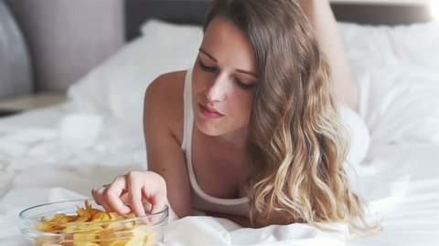 Girl eating chips lying on the bed