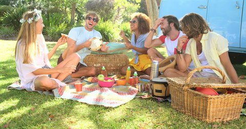 Group of hipster friend laughing and having a picnic at a music festival