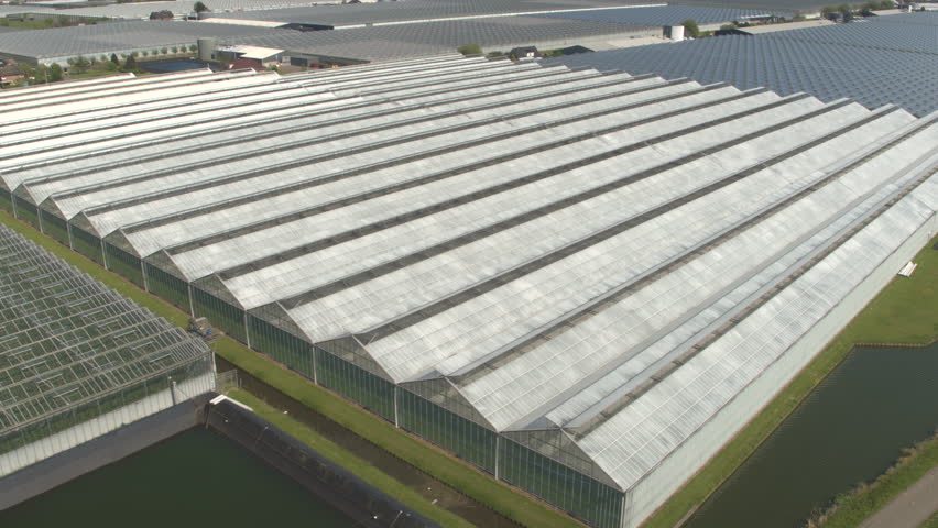 AERIAL: Flying above beautiful vast modern plantation of stunning glass greenhouses on sunny spring day. Organic cultivation of natural and fresh vegetables, greenery and plants on sun light and heat | Shutterstock HD Video #18133555