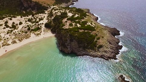 Aerial view from the popular Voidokilia beach in Peloponnese, Greece. A half-moon-shaped beach surrounded by vivid water in an unrealistic way. Camera rotates along the coastline.