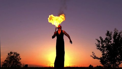 Fantastic Show at Sunset. Circus on Stilts Spit the Fire. the Action in Slow Motion.