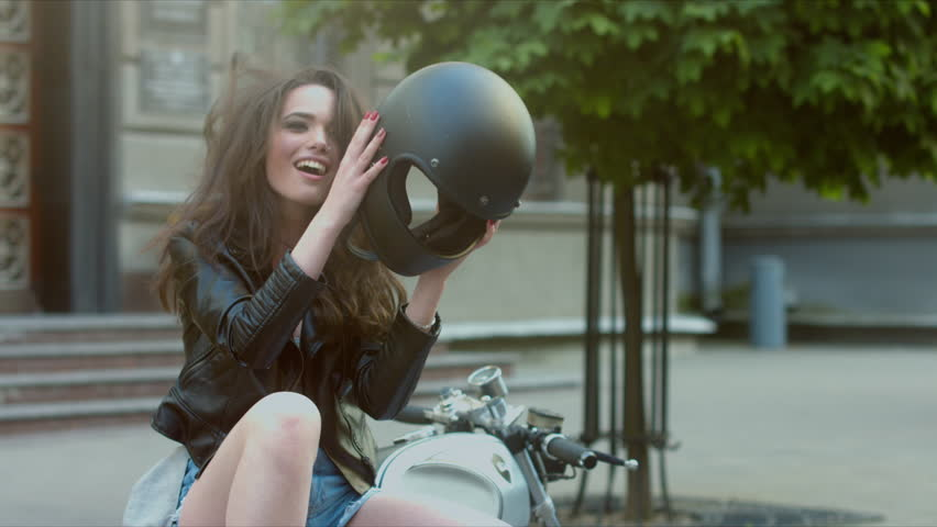 MED Urban portrait of a beautiful Caucasian girl on a motorcycle. Gorgeous brunette female in leather jacket, taking off motorcycle helmet, then laughs. 60 FPS 4K UHD | Shutterstock HD Video #18183259