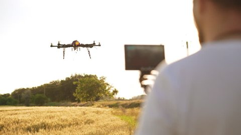 Young man controling drone in field at sunset. Slow motion Close up.