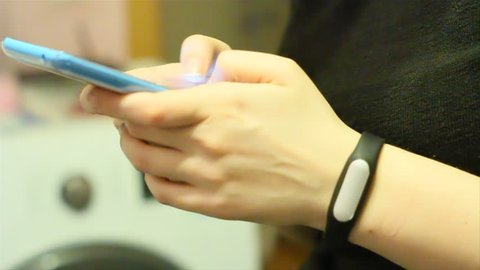 Woman's hands with fitness band typing a message on a smartphone. Close up