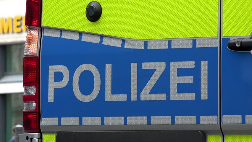 Warning lights flash on blue German law enforcement vehicle stopped roadside.