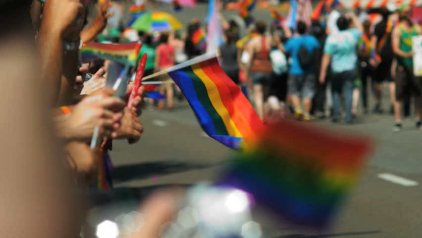 DENVER, COLORADO CIRCA JUNE 2016 - people clap, cheer and hold rainbow flags as gay pride parade marchers walk by during Pridefest festivities slow motion 60fps
