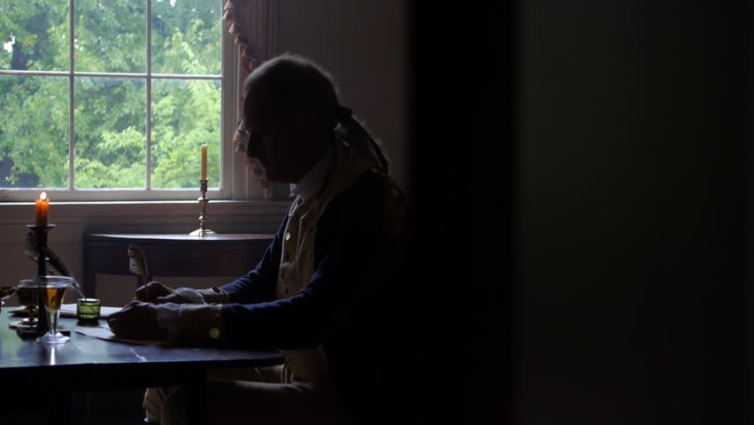VIRGINIA - OCTOBER 2014 - Reenactment, President, founding father, Revolutionary War anniversary recreation -- Tabletop, quill writing, dipping ink and writing by candle light & by window, standing
