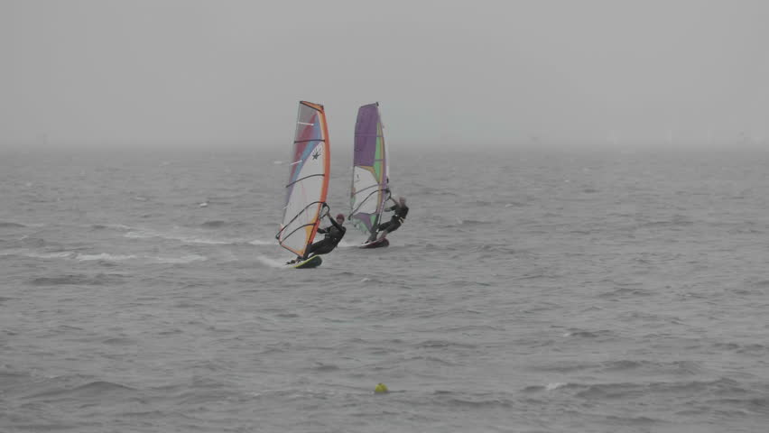 Hutchinson Island, FL/US - July 23, 2016 [Local windsurfers take advantage of the gusty winds and rainy weather as a tropical disturbance moves through southern Florida.] | Shutterstock HD Video #18252427