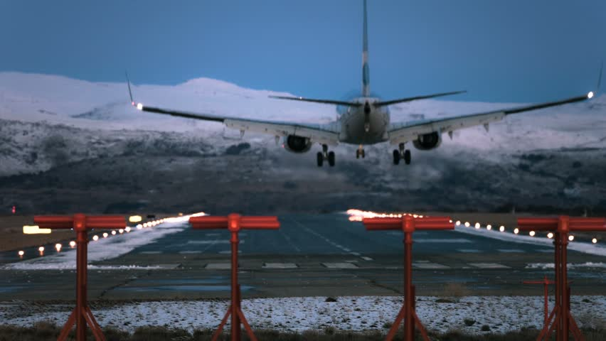 Plane landing at airport scenic landscape snowed mountains night background view from behind