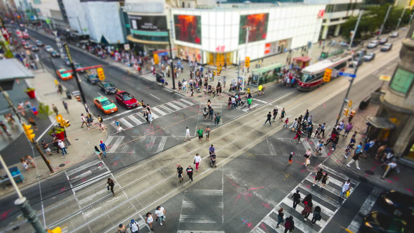 Toronto, Canada - June 26, 2016: Time lapse view of people and traffic crossing busy intersection at Yonge-Dundas Square in Toronto, Ontario, Canada.