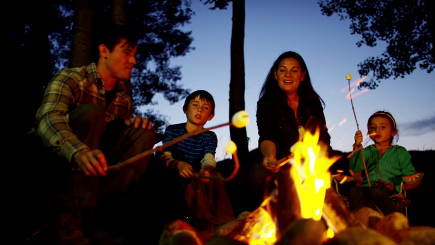 American Caucasian family enjoying camping and toasting smores outdoors