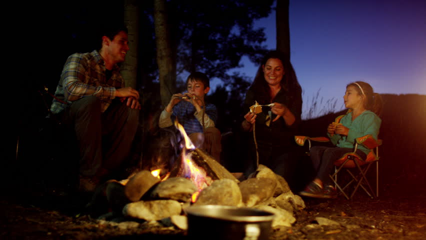 Happy Caucasian parent and children camping and eating smores on holiday outdoor