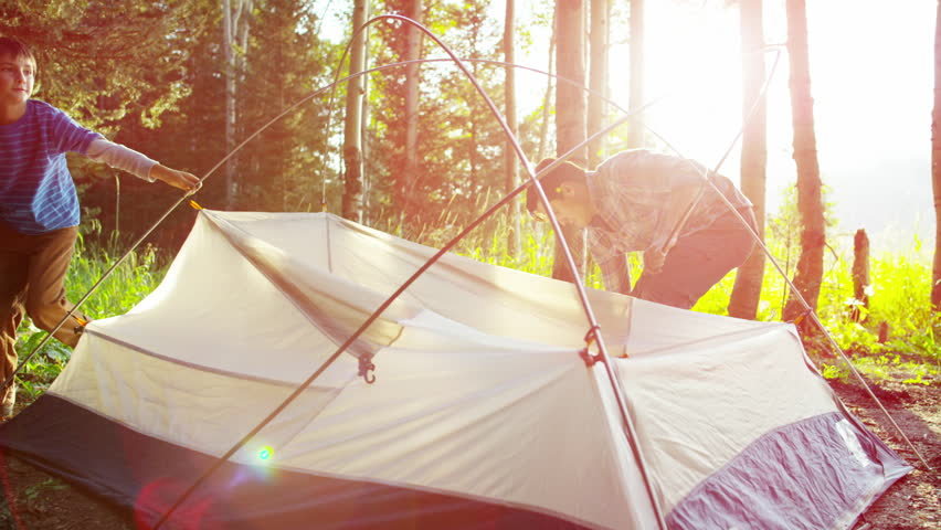 American Caucasian father and son erecting tent together on vacation outdoor