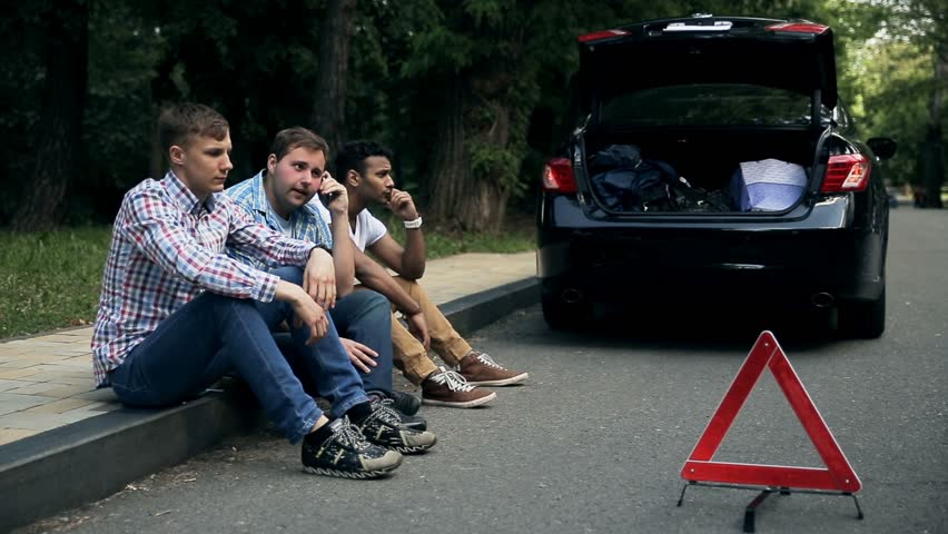 young men sit on roadside car is broken down