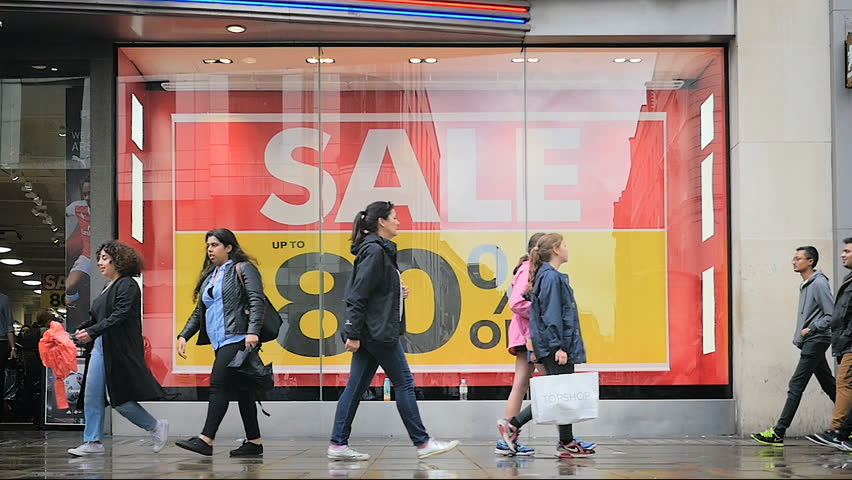 LONDON, UK - 13 JULY 2016: Slow motion (1/4 speed) video footage of shoppers on London's busy Oxford Street shopping district on a wet day with a shop frontage advertising a sale in the background.