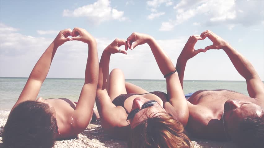 Beautiful Happy young family father, mother and little son making heart shape with their hands over sea background. Tanning together. Vacation concept. Summer holidays. Tourism. Slowmo 240 fps 1080p