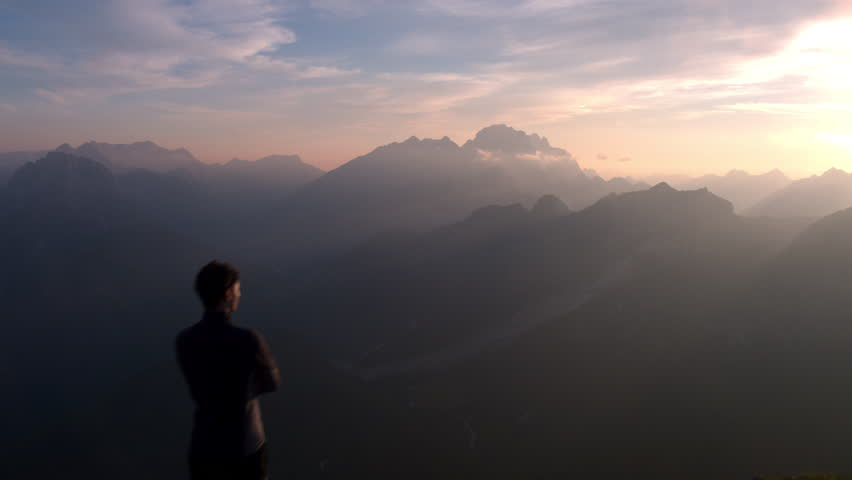 Aerial - Flyover hiker standing on top of the mountain and watching beautiful sunset after reaching the top | Shutterstock HD Video #18379705