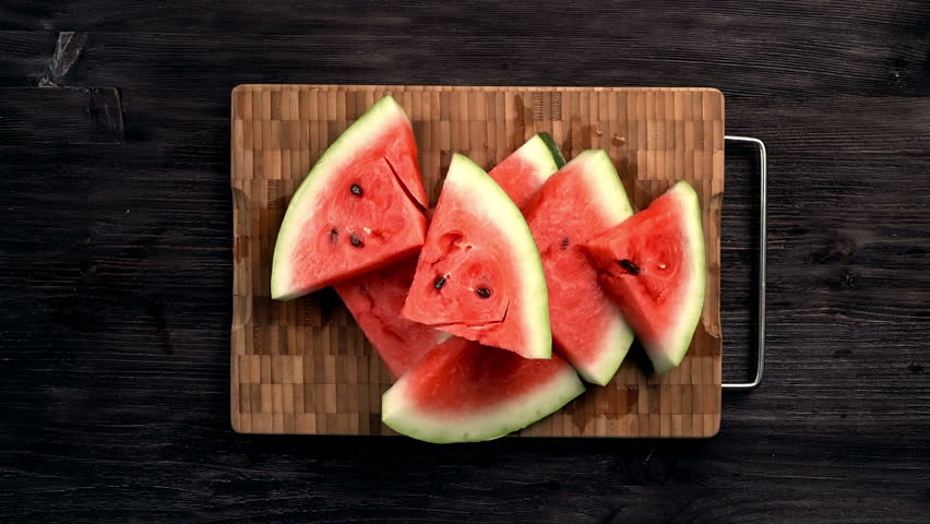 The company of people takes cut pieces of juicy ripe watermelon on black table, flat lay, top view. 4k | Shutterstock HD Video #18380203
