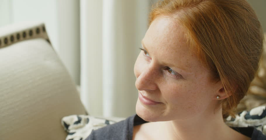 Slow motion closeup shot of a young redhead woman smiling at the camera.   Shutterstock HD Video #18418405