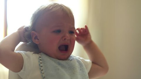 Upset cute baby coughing. beautiful adorable toddler baby coughs as he cries