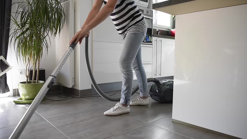 young woman wiping floor with mop and bucket at home, focus on