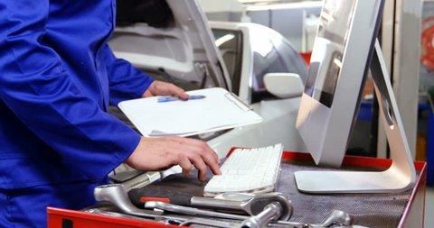 Caucasian mechanic preparing a check list while servicing a car engine in repair shop 4k