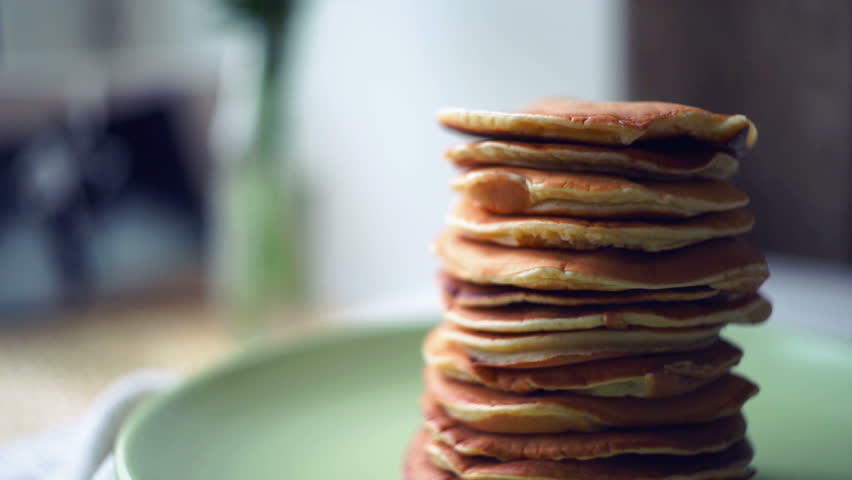 Baking american pancakes on a in a frying pan stock footage video pancakes stack on green plate at kitchen table close up of sweet american pancakes ccuart Choice Image