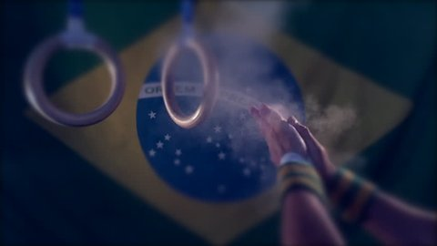 Taped hands of gymnast clapping white chalk powder into a cloud under gymnastic rings in front of a dark Brazil flag background