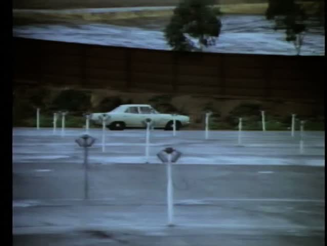 1970s car driving along empty drive-in