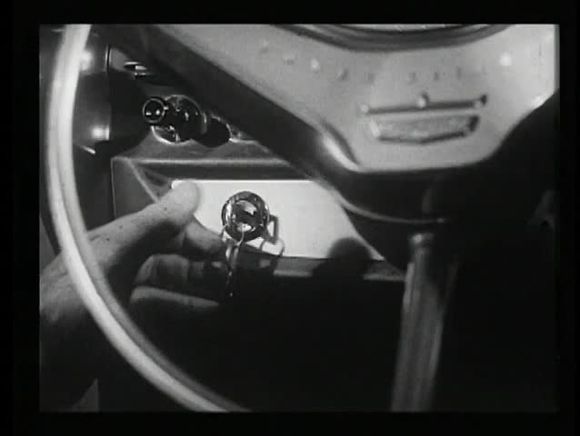 Close-up of hand turning ignition key in 1960s car