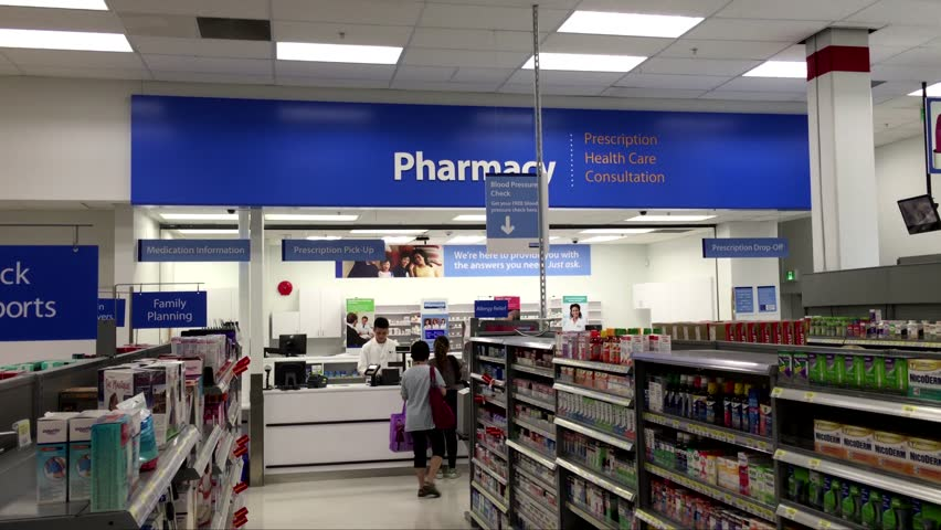 Coquitlam, BC, Canada - July 27, 2016 : People line up for picking up their prescription medicine inside Walmart pharmacy