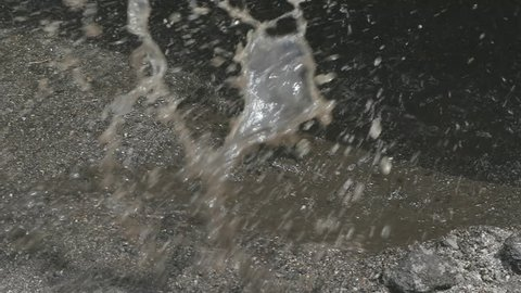 Tire Hits Puddle Pothole in Slow Motion Close Up. a close up of a pothole filled with water. Truck tires hit it in slow motion splashing water everywhere