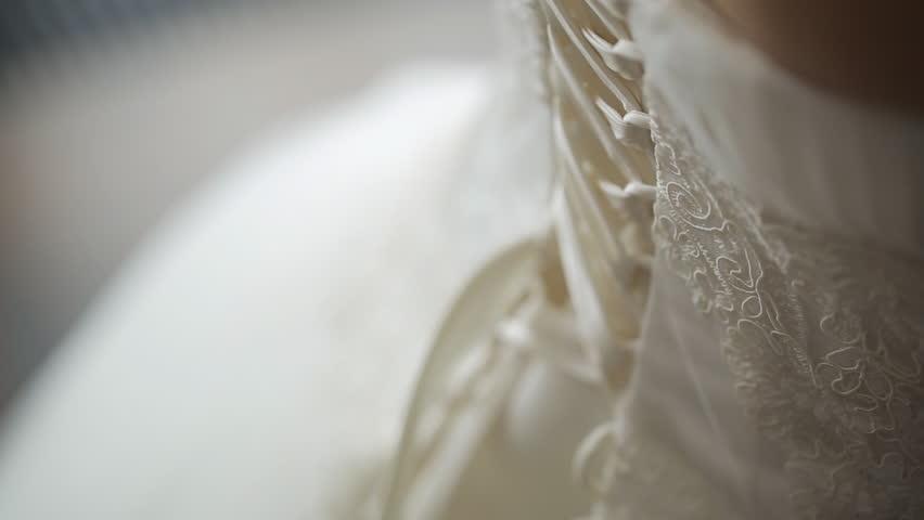 Mother helps her daughter to fasten foundation garment on her wedding dress.