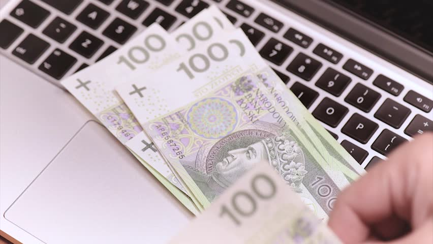 Male hands counting Polish money banknotes at the table in front a laptop computer. Man with money zloty and notebook.