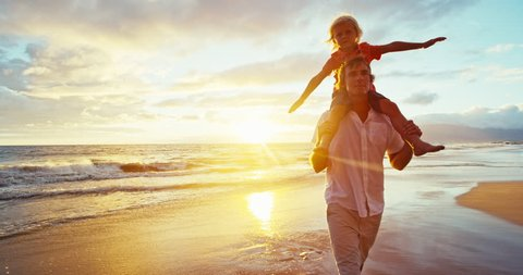 Happy father and son playing on the beach at sunset