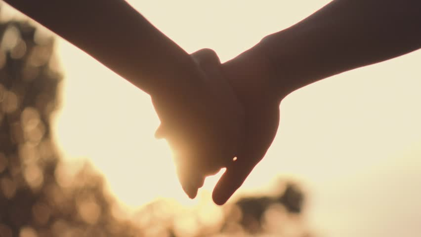 Close up of two Lovers Joining Hands. SLOW MOTION 240 fps. Detail Silhouette of Man and Woman holding hands over the Sunset Lake Background. Couple Trust, Love and Happiness concept.