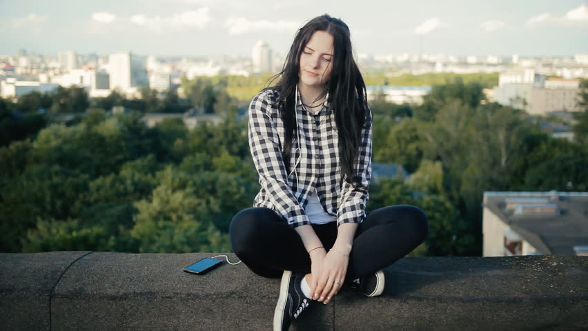 Girl listening to music with headphones on the roof   Shutterstock HD Video #18600005