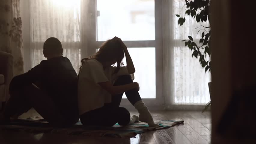 Man and woman sitting on the floor back to back | Shutterstock HD Video #18600425