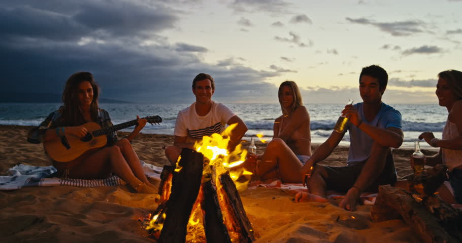 Young People Dance And Sing On The Beach. Camping On The ...