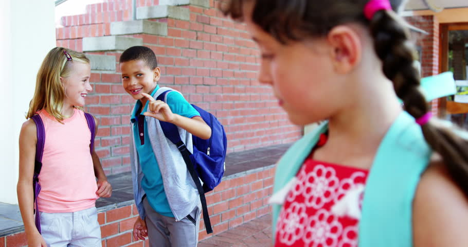 Slow motion of schoolkid bullying a sad girl in corridor at school 4k