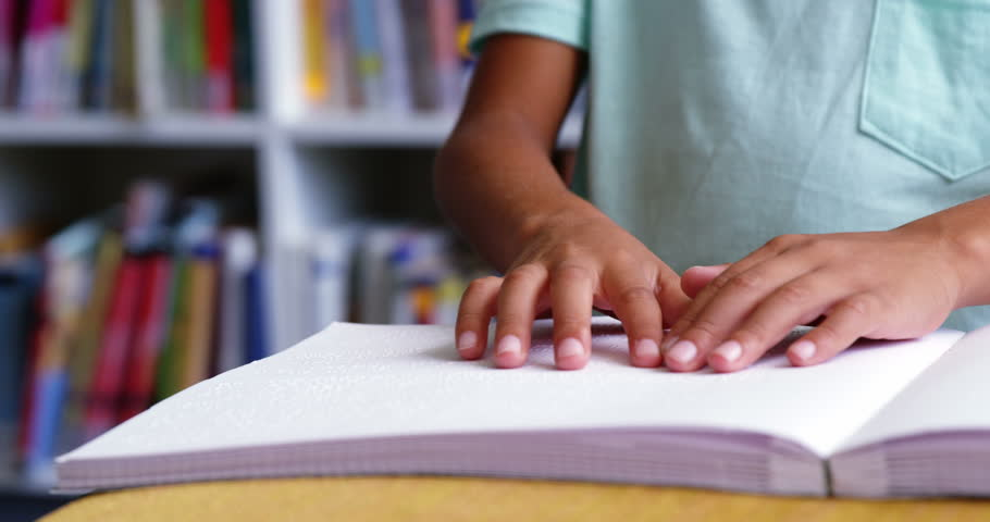 Slow motion of school kid reading a braille book in classroom at school 4k