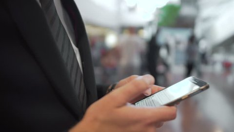 Businessman searching info on smartphone while others stand in line, gadgets. Office worker waiting for bus outside, typing message, making to do list online application, planning day, browsing site