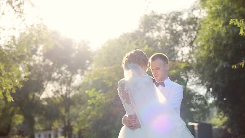 Attractive wedding couple holding by hands and whirling on the green meadow at sunset | Shutterstock HD Video #18713375