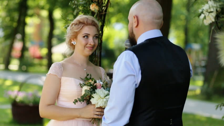 Handsome Groom Declaring At The Outdoors Wedding Ceremony While Charming Bride Tenderly Looking Him Stock Footage Video 18717155