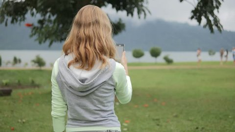 Young woman looking at map and playing an augmented reality mobile game on a phone walking around in the park. Using location based app with camera to interact on smartphone
