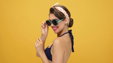 Sexy young gorgeous pinup girl showing silence gesture, taking off her sunglasses and winking